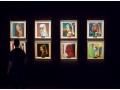 Zdjęcie z wystawy malarstwa Nareka Avetisiana, Simulacrum. 33 Faces, przedstawiające prace na ciemnej ścianie.