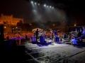 Zdjęcie z koncertu Big Lao Che Band. Na pierwszym planie na scenie muzycy, w tle publiczność i podświetlony Zamek Lubelski.