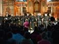 Zdjęcie z koncertu zespołu Lekso Gremelaszwili i Męski Zespół Wokalny KAIROS, na którym widać kilkunastu mężczyzn ubranych na czarno wykonujących pieśń. Na pierwszym planie publiczność.