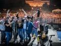 Członkowie zespołu Big Lao Che Band na scenie podnoszą w górę ręce i instrumenty. W tle publiczność oraz podświetlony Zamek Lubelski. fot. R. Grablewski