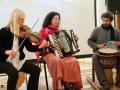Zdjęcie z wydarzenia Opowieści Wschodniej Treści przedstawiające muzyków: dwie kobiety, które grają na skrzypcach i akordeonie oraz mężczyznę grającego na bębnie.