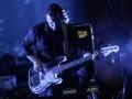Zdjęcie z koncertu zespołu Goldfrapp, na którym mężczyzna stojący na scenie gra na gitarze elektrycznej.