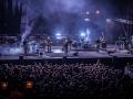 Zdjęcie z koncertu Alison Goldfrapp, na pierwszym planie publiczność odwrócona od obiektywu, która patrzy na scenę. Scena jest spowita mgłą, na tle ciemnej scenografii gra zespół.