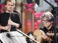 Zdjęcie z koncertu zespołu Lekso Gremelaszwili i Męski Zespół Wokalny KAIROS przedstawiające dwóch mężczyzn, którzy grają na instrumentach przypominających flet oraz bandżo.