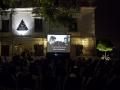 Zdjęcie z projekcji filmu w ramach cyklu Move East Movie przedstawiające ekran z obrazem oraz publiczność.