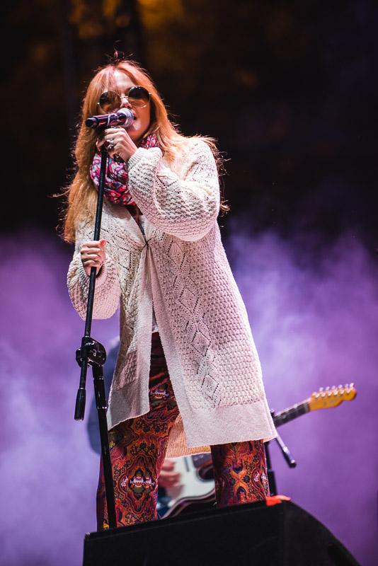 """Specjalna festiwalowa produkcja pn. """"Wojna to przeżytek"""".Na zdjęciu widzimy wokalistkę, Anie Rusowicz śpiewającą do mikrofonu. Za nią, rozmazana sylwetka gitarzysty stojącego w podświetlonym dymie."""