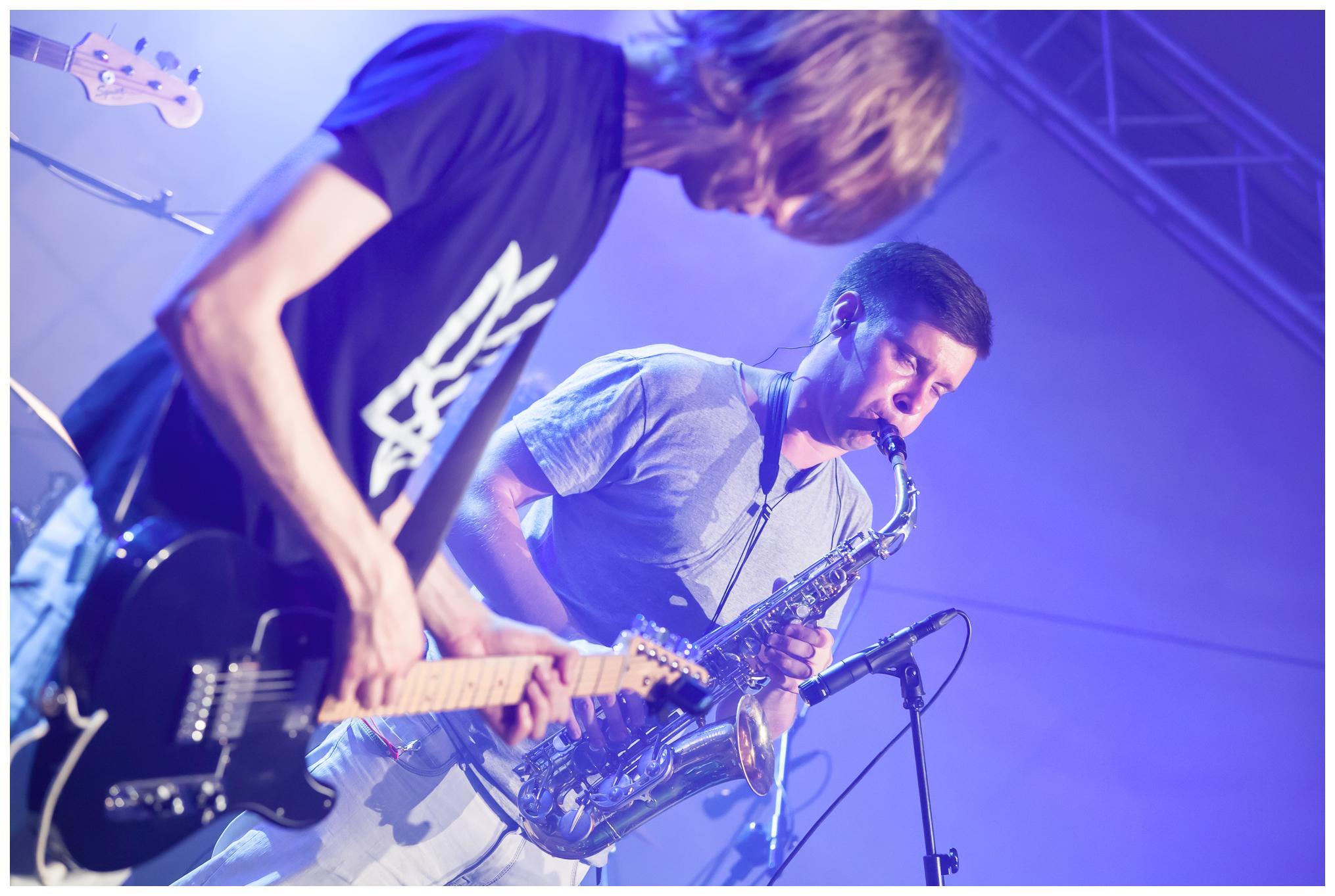 Koncert zespołu Atomic Simao. Na zdjęciu widzimy dwóch muzyków. Jeden gra na gitarze, drugi na saksofonie.