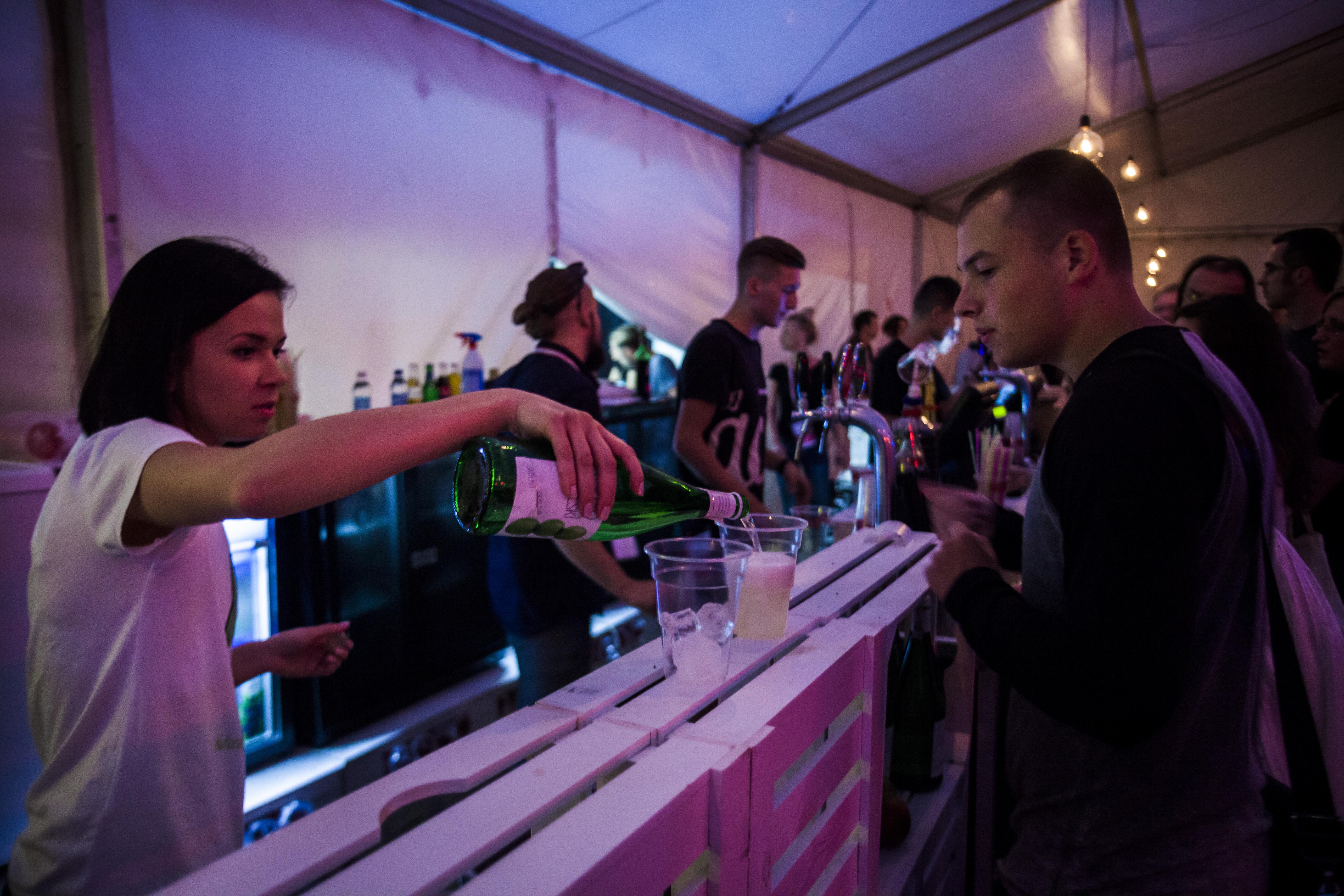 Na zdjęciu widać gości festiwalu podczas zamawiania drinków oraz jedzenia. Na pierwszym planie widzimy panią rozlewającą Cydr Lubelski do szklanek.