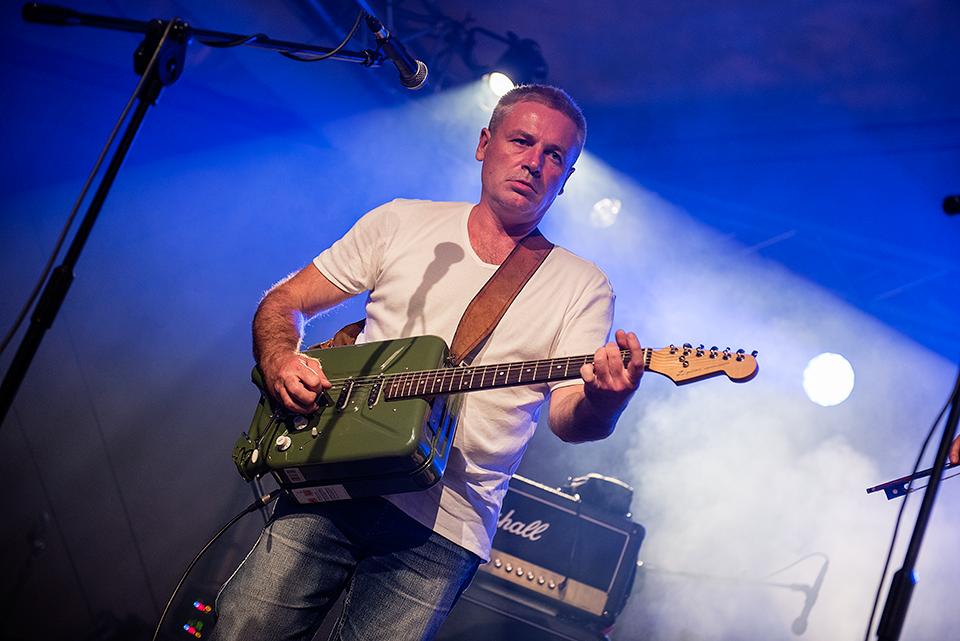 Koncert zespołu DG 307. Na zdjęciu widać muzyka grającego na unikalnej gitarze, zrobionej z kanistra na paliwo.