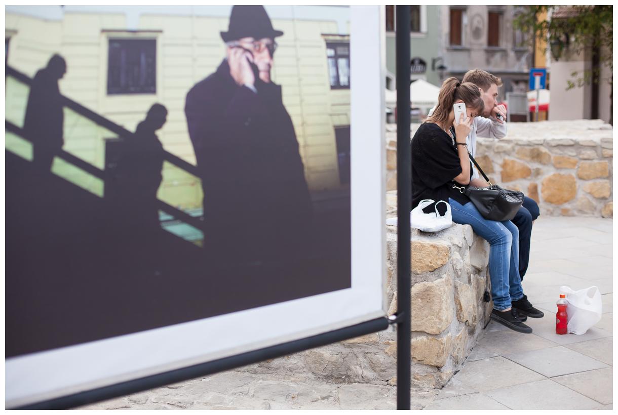 Ponownie zdjęcie z wystawy. Na pierwszym planie olbrzymia fotografia mieszcząca się na Placu po farze. Ukazuje ona mężczyznę oraz cienie dwóch osób. Obok fotografii siedzą młodzi ludzie.