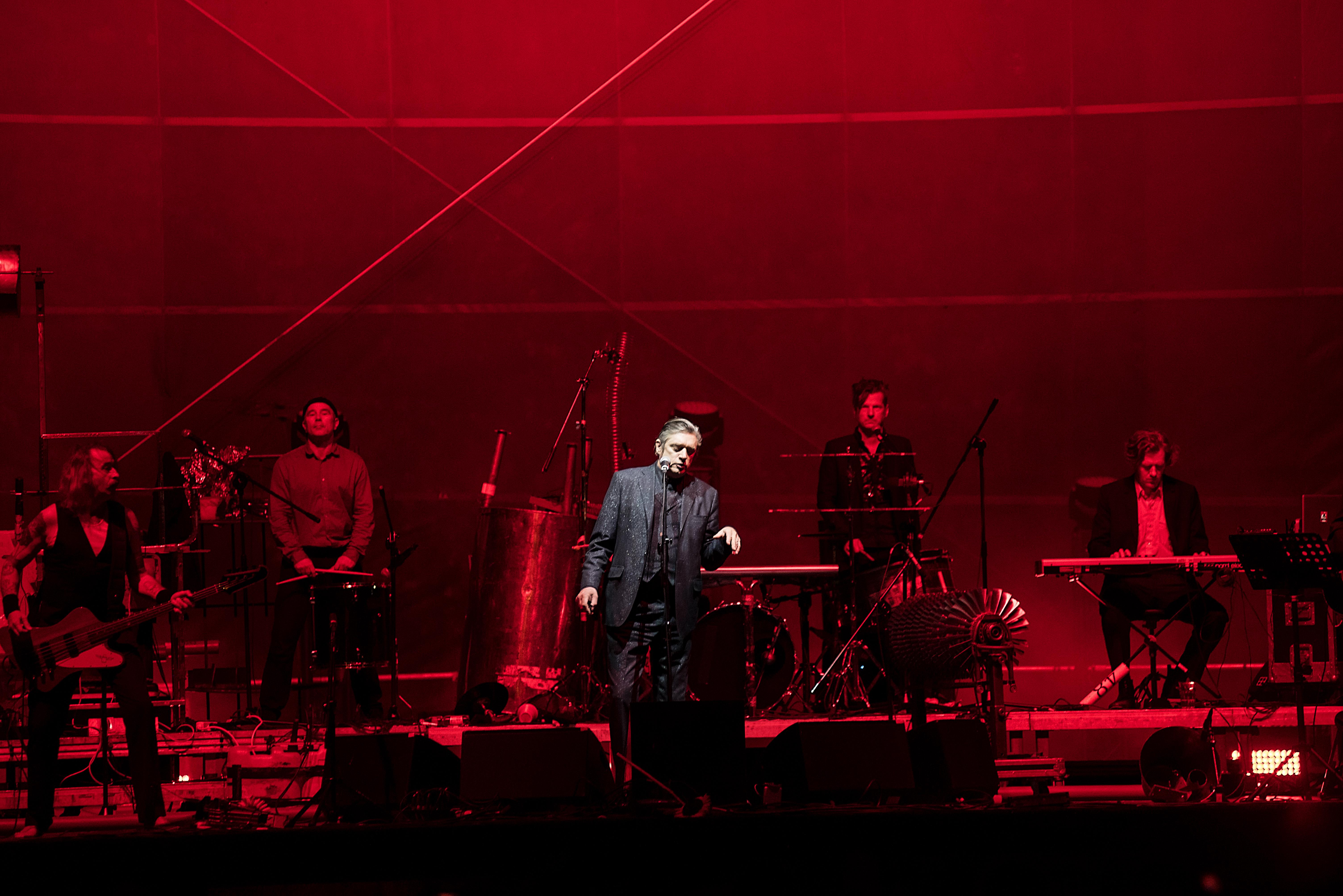 Ponownie zdjęcie z koncertu Einsturzende. Przedstawia ono wszystkich członków zespołu grających na instrumentach. Scena oświetlona jest na czerwono.