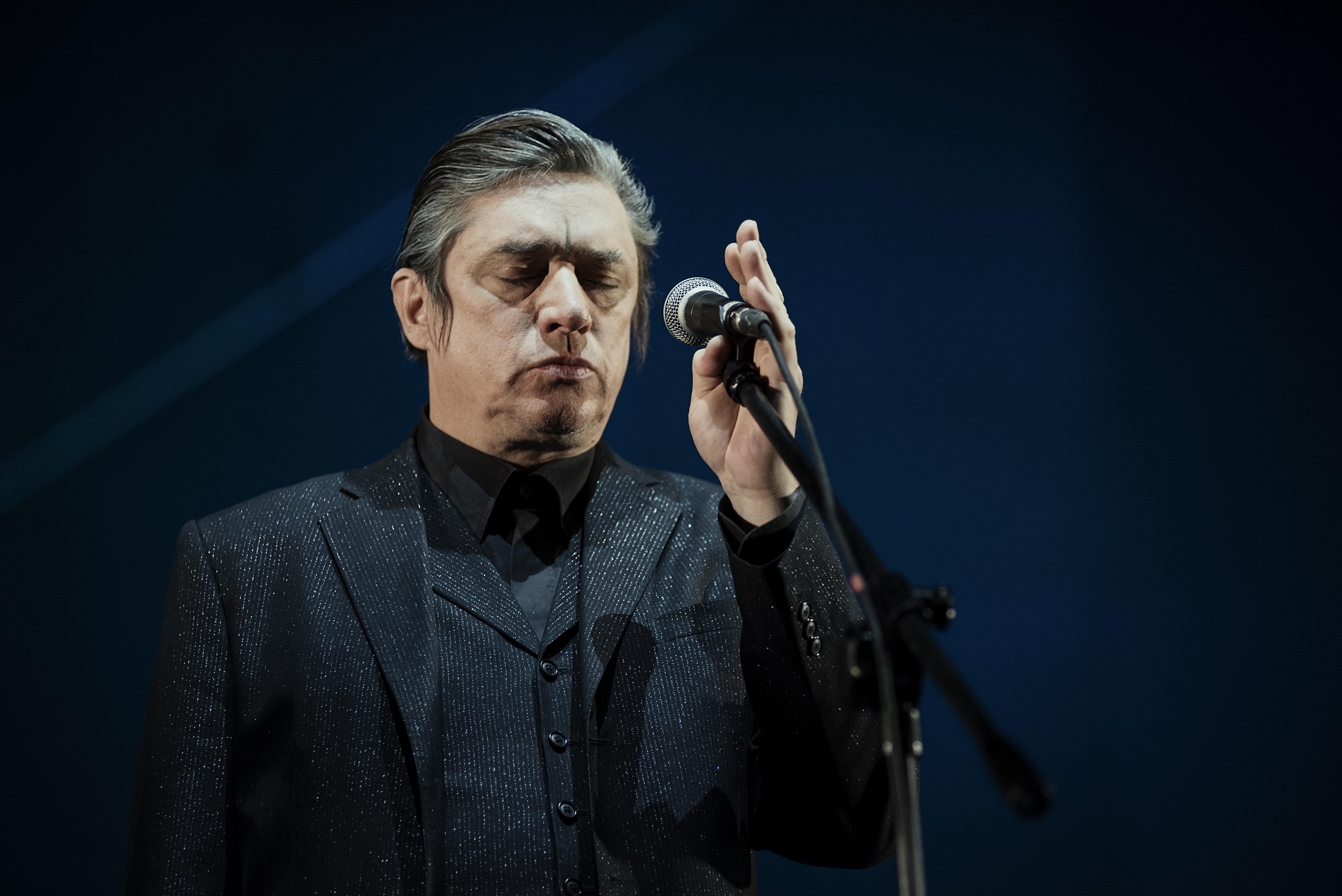 Koncert zespołu Einsturzende.Na zdjęciu widać wokalistę, który stoi przed mikrofonem z zamkniętymi oczami.