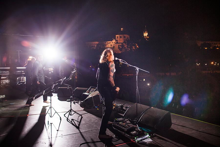 Zdjęcie z koncertu wykonane ze sceny, przedstawia zarówno grających artystów jak i publiczność zgromadzoną przed nimi.