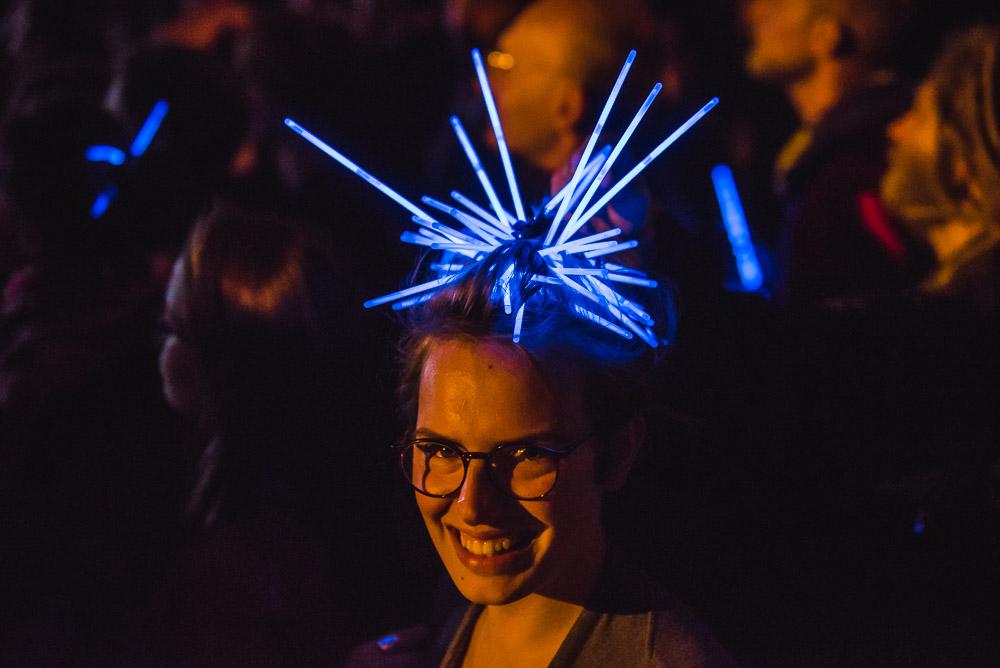 Zdjęcie publiczności podczas koncertu. Na pierwszym planie uśmiechnięta kobieta ze świetlnymi dekoracjami na głowie, w tle pozostali ludzie.