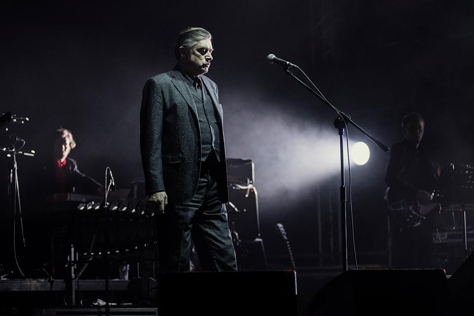 Zdjęcie z koncertu Einsturzende. Zbliżenie na wokalistę. Na drugim planie widać klawiszowca oraz gitarzystę.