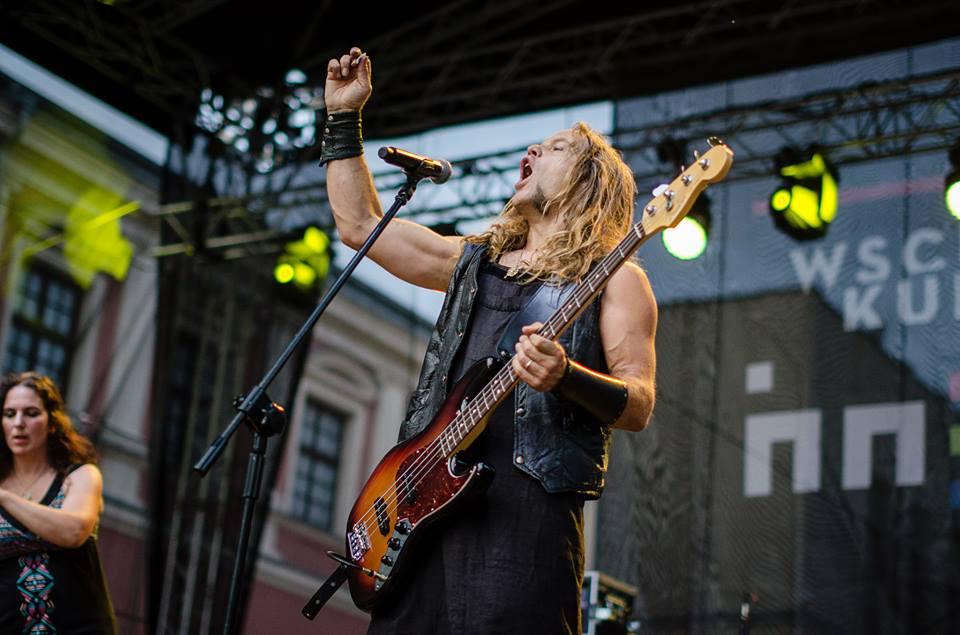 Koncert zespołu FaunFables. Na zdjęciu widzimy wokalistę śpiewającego do mikrofonu oraz trzymającego gitarę w ręce.