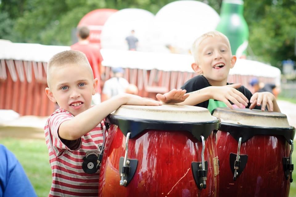 Zdjęcie ukazujące dzieci podczas Małych Innych Brzmień - projektu muzycznego dla dzieci. Dwóch chłopców gra na bębnach.