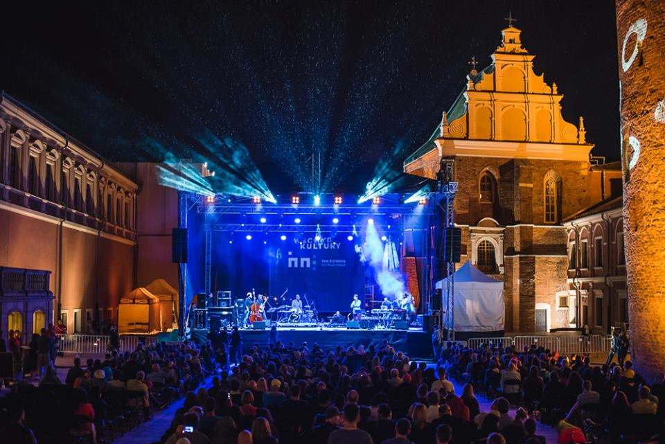 Na zdjęciu widzimy scenę na Zamku Lubelskim. Magicznie oświetlona scena na niebiesko i ciepłe żółte oświetlenie zamku tworzą idealny klimat towarzyszący imprezie muzycznej.