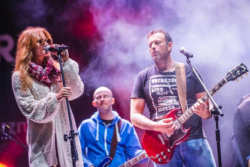Zdjęcie przedstawia śpiewającą Annę Rusowicz oraz Tymona Tymańskiego, grającego na gitarze. W tle drugi gitarzysta.
