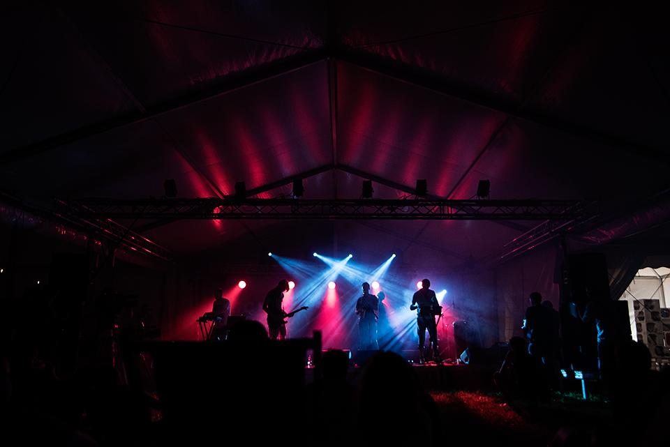 Zdjęcie zespołu Atomic Simao. Widzimy wszystkich członków zespołu na scenie. Grają na swoich instrumentach, tj. gitarach, klawiszach, bębnach.