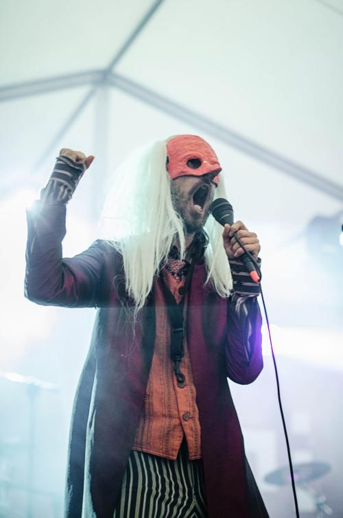 Zdjęcie z koncertu zespołu Kabaret-Dr.-Caligariho. Widzimy wokalistę, który śpiewa do mikrofonu w białej prostej peruce oraz pomarańczowej masce karnawałowej na oczach.