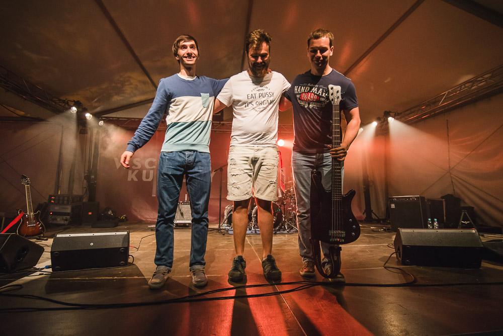 Koncert zespołu Kasai. Trzech muzyków stoi na scenie. Jeden ma gitarę, wszyscy trzymają się pod ramię z uśmiechem na twarzy.