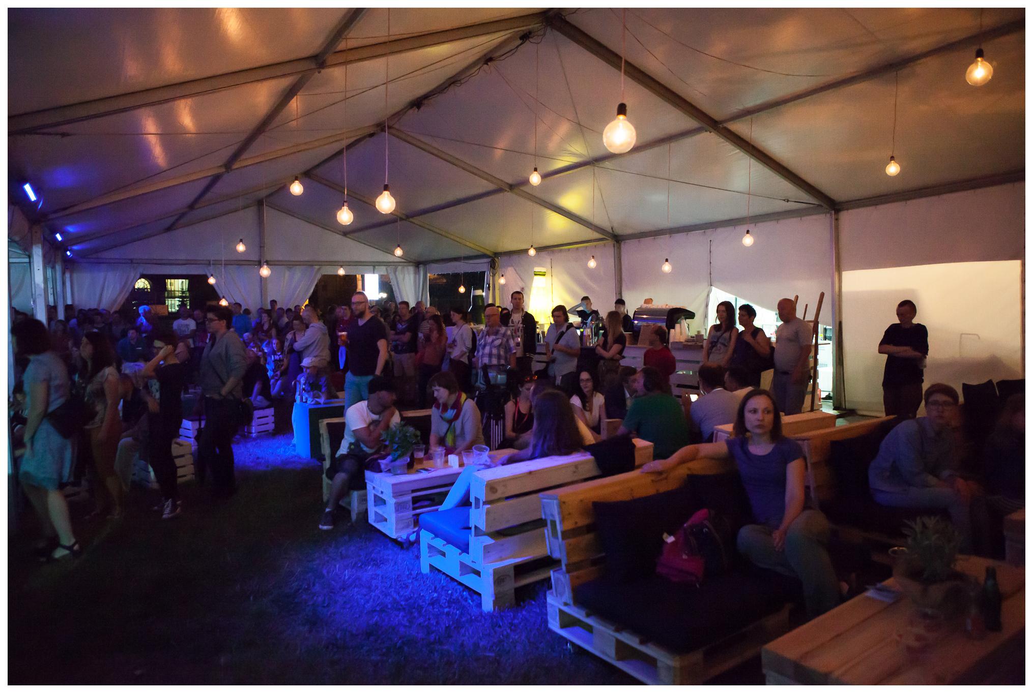 Zdjęcie klubu festiwalowego oraz zgromadzonych uczestników wydarzeń muzycznych.