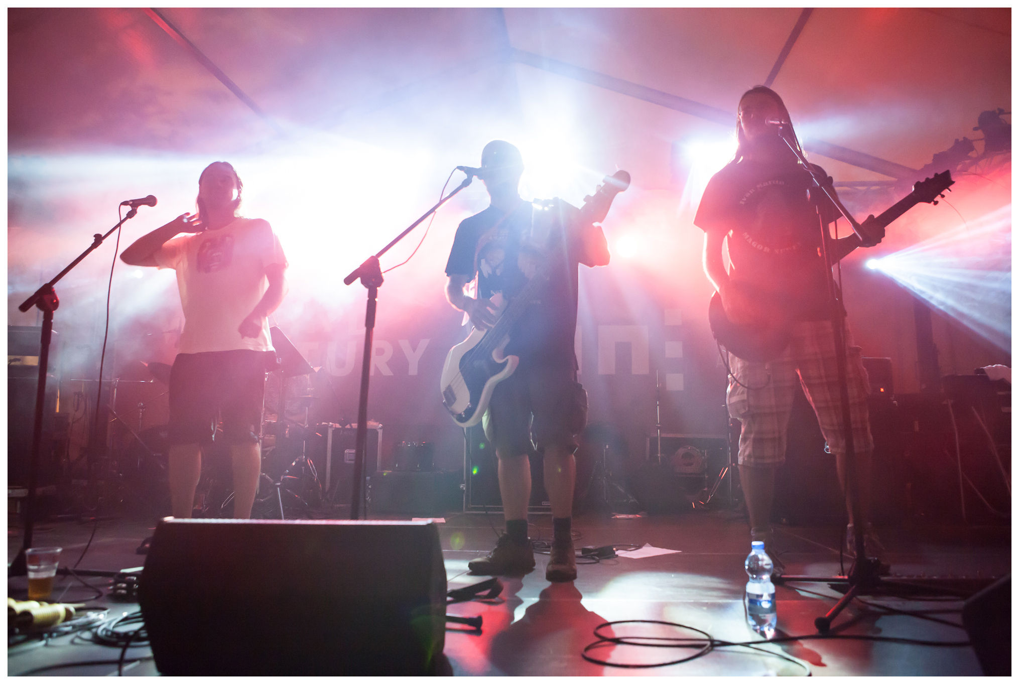 Koncert zespołu Nevypar Kovatjezd. Na scenie widzimy czterech artystów. Dwóch muzyków gra na gitarach, jeden na perkusji, jest też wokalista.