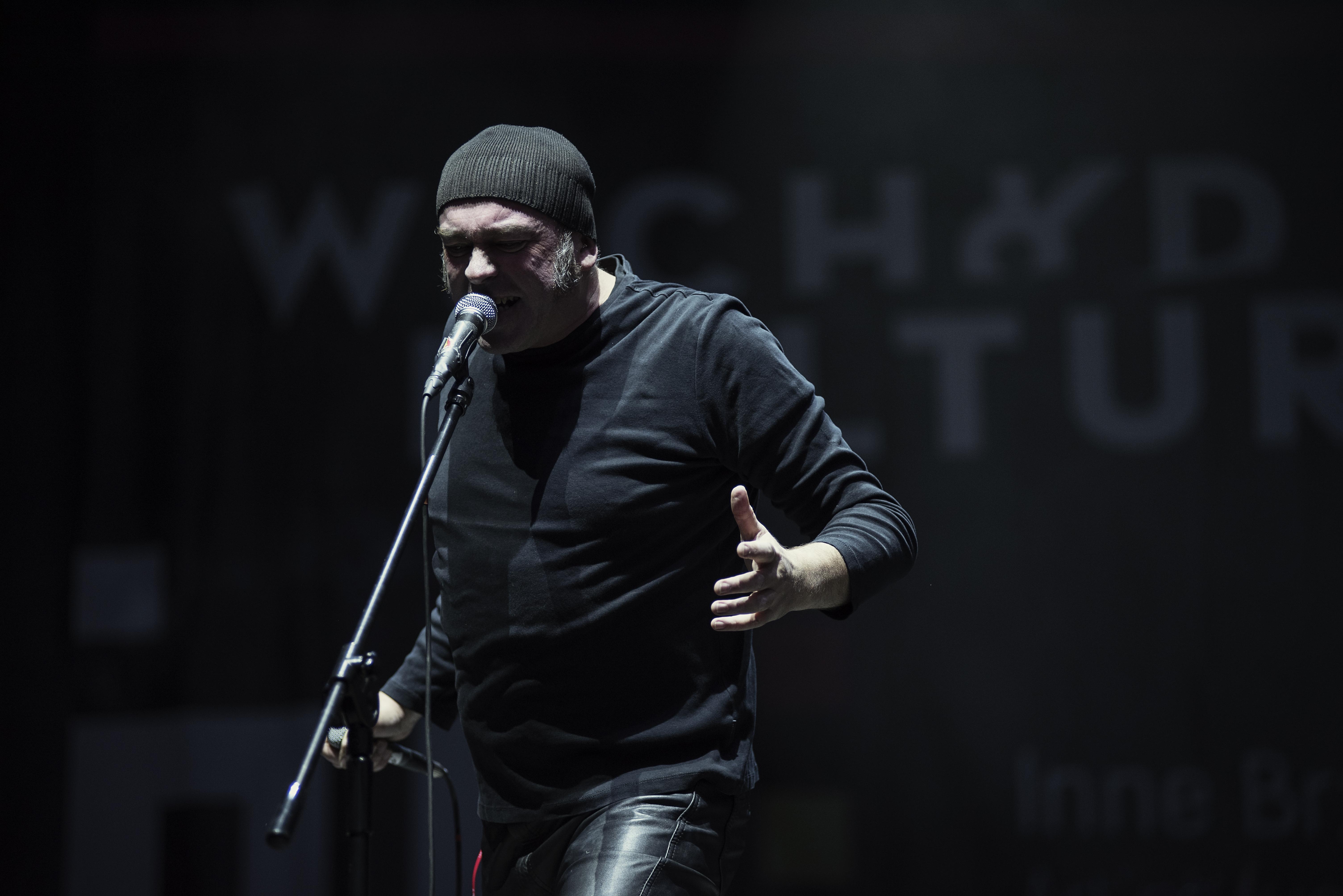 Ponownie zdjęcie z projektu muzycznego Rimbaud. Widzimy wokalistę przodem. Śpiewa do jednego mikrofonu, drugi zaś nadal trzyma w ręce.