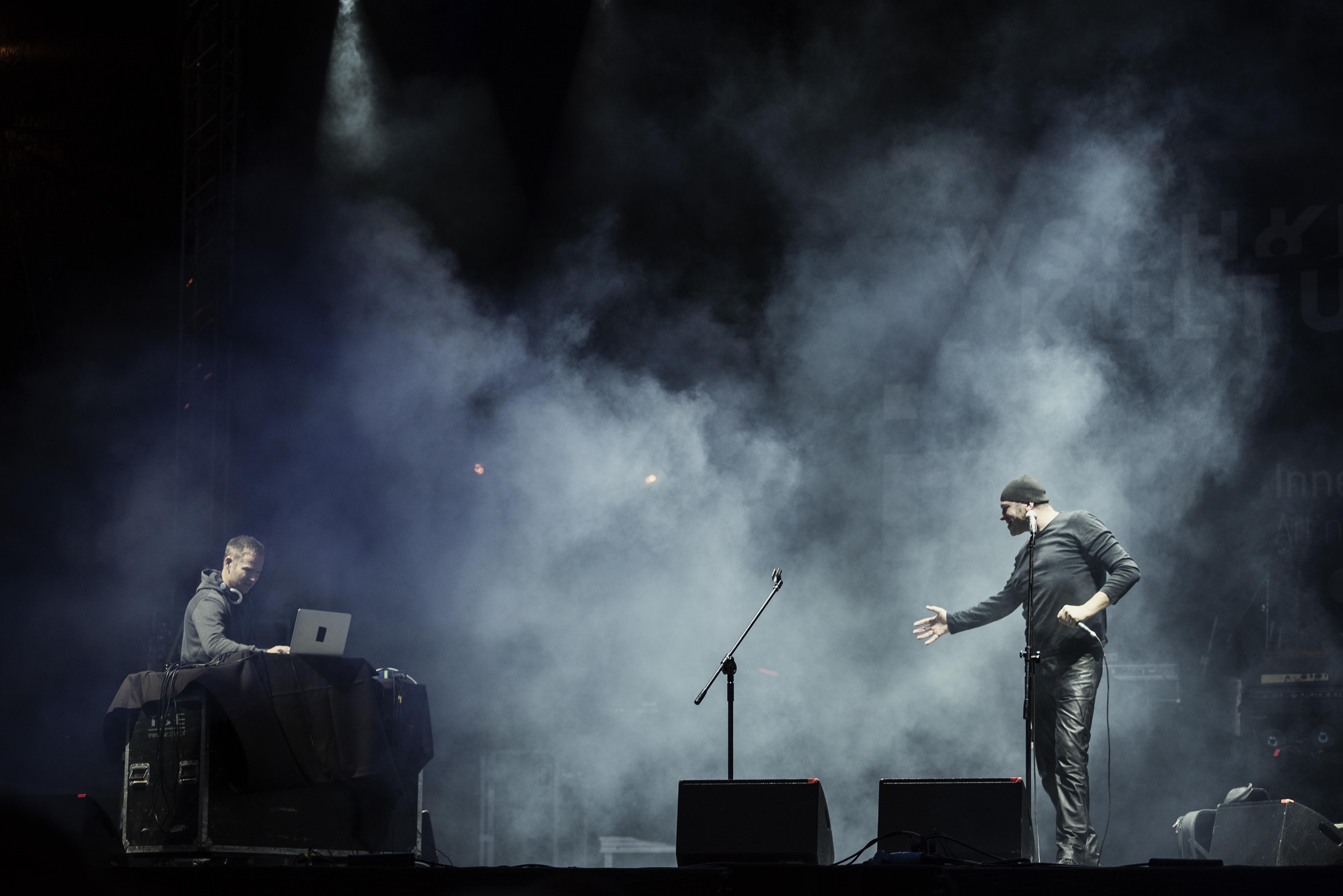 Projekt Rimbaud. Zdjęcie ukazujące wokalistę, który trzymając mikrofon w ręce, wykonuje ruch w stronę muzyka będącego na scenie razem z nim. Siedzi on na przeciwko miksera, laptopa.