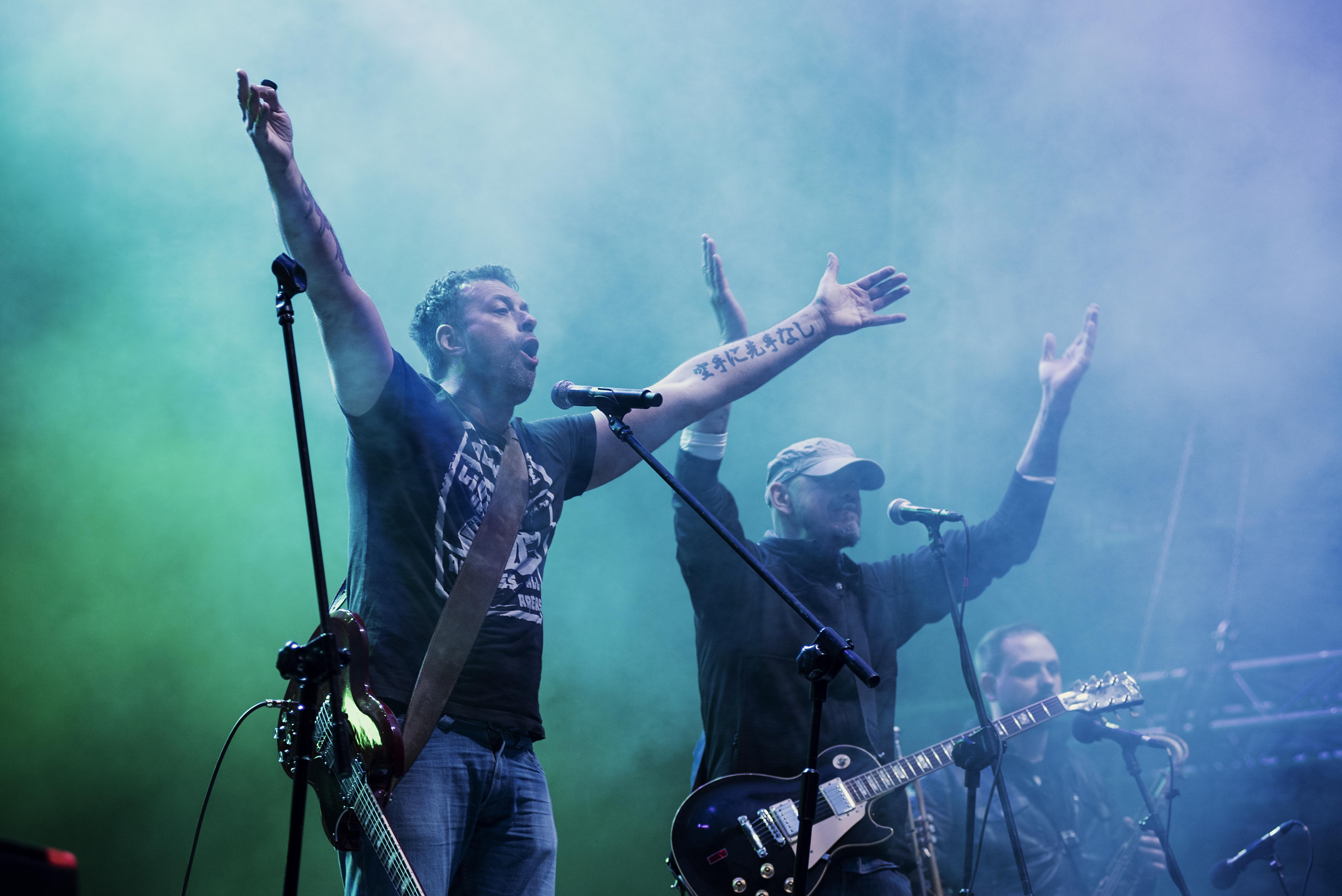 Zdjęcie ukazuje Tymona Tymańskiego wraz z dwoma innymi muzykami. Dwóch z nich ma uniesione do góry ręce, jakby mieli klaskać w górze.