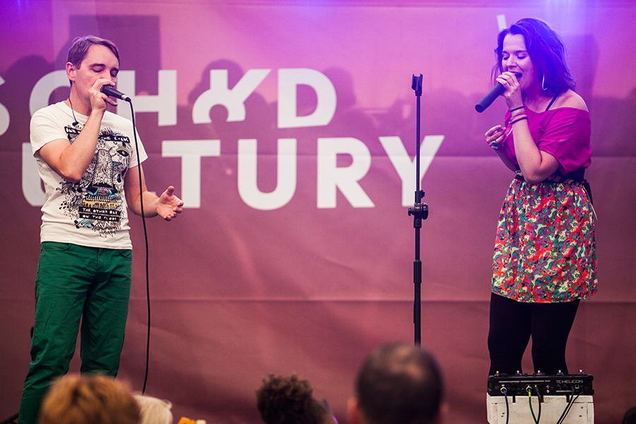Występ zespołu me mysefl and I. Widzimy śpiewającego mężczyznę oraz kobietę, którzy stoją w znacznej odległości od siebie.