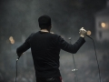 Projekt Rimbaud. Zdjęcie wykonane ze sceny, zza pleców wokalisty, który trzyma dwa mikrofony w dłoniach. Przed nim rozmazane twarze ludzi z publiczności.