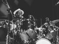 Czarno- białe zdjęcie przedstawiające fragment koncertu perkusisty ( Tony Allen) z jego dziesięcioosobową orkiestrą. Przy perkusji siedzi Tony Allen i gra na instrumencie.