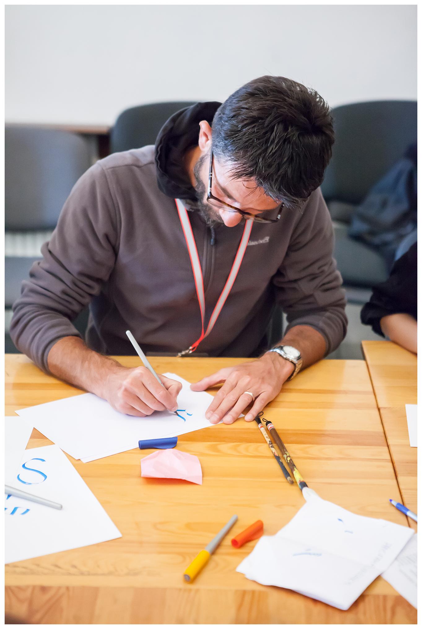 Warsztaty kaligrafii oraz pisma ormiańskiego. Na zdjęciu widzimy jednego z uczestników warsztatu, który pisze literę na kartce.