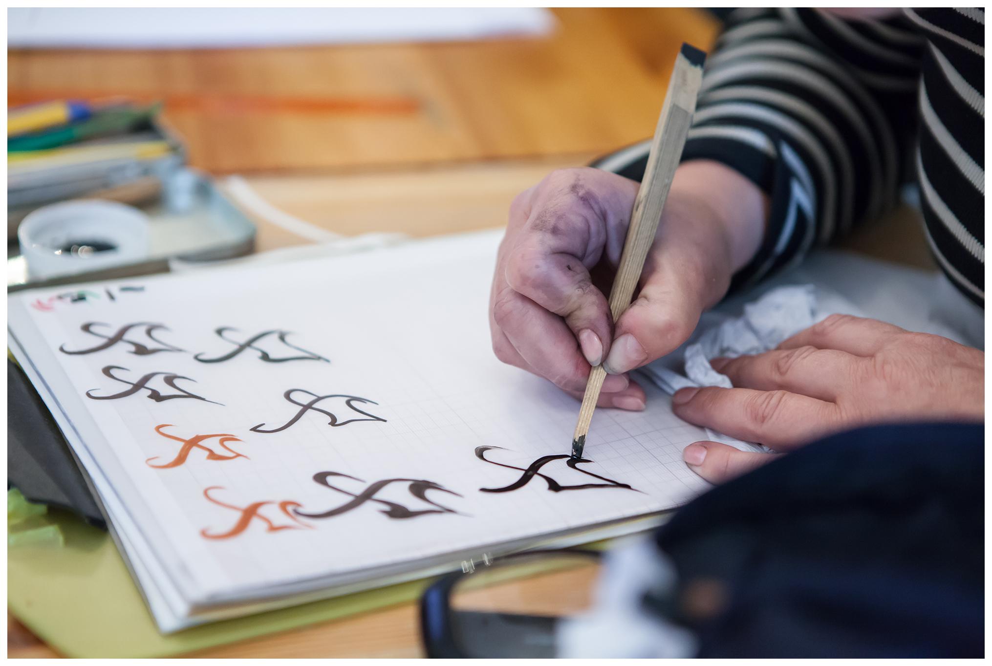 Zbliżenie na dłonie kobiety oraz litery naniesione czarnym i czerwonym tuszem za pomocą drewnianej listewki na papier.