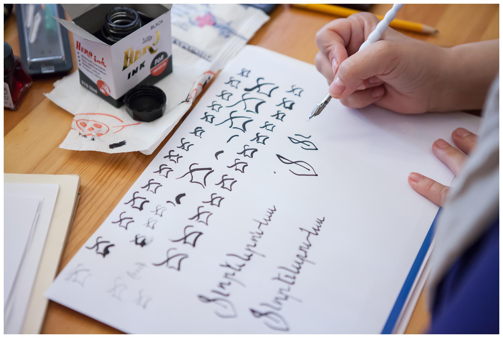 Zdjęcie ukazuje dłonie innej kobiety, która nanosi litery na papier za pomocą pióra.