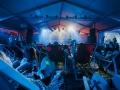 [Zdjęcie z perspektywy publiczności. Widzowie leżą na leżakach. Na dalszym planie zespół gra na scenie. Wszyscy oświetleni są niebieskim światłem.]