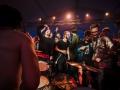 [Roztańczony i podekscytowany tłum ludzi otacza perkusistę. Artysta siedzi bez koszulki tyłem do obiektywu.]