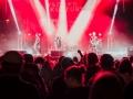 [Zespół występujący na scenie oświetlony mocnym czerwonym światłem oraz publiczność zebrana pod sceną. W tle logo festiwalu.]