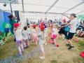 [Na zdjęciu grupka dzieci wraz z prowadzącym uchwyceni w tanecznych pozach. Dzieci naśladują prowadzącego, który pokazuje im co mają robić. W tle sylwetki osób zebranych pod namiotem.]