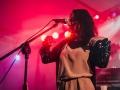 [Zbliżenie na kobietę stojącą przed mikrofonem w pozycji tańczącej. W tle różowe oświetlenie.]