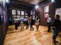 [Zdjęcie przedstawia ludzi przyglądających się wystawie, to jest plakatom zawieszonym na ciemnej ścianie.]