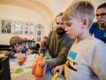 [Zdjęcie przedstawia dzieci i dorosłych podczas warsztatu Marchew Mellody. Uczestnicy wspólnymi siłami starają się zrobić instrument z marchewki.]