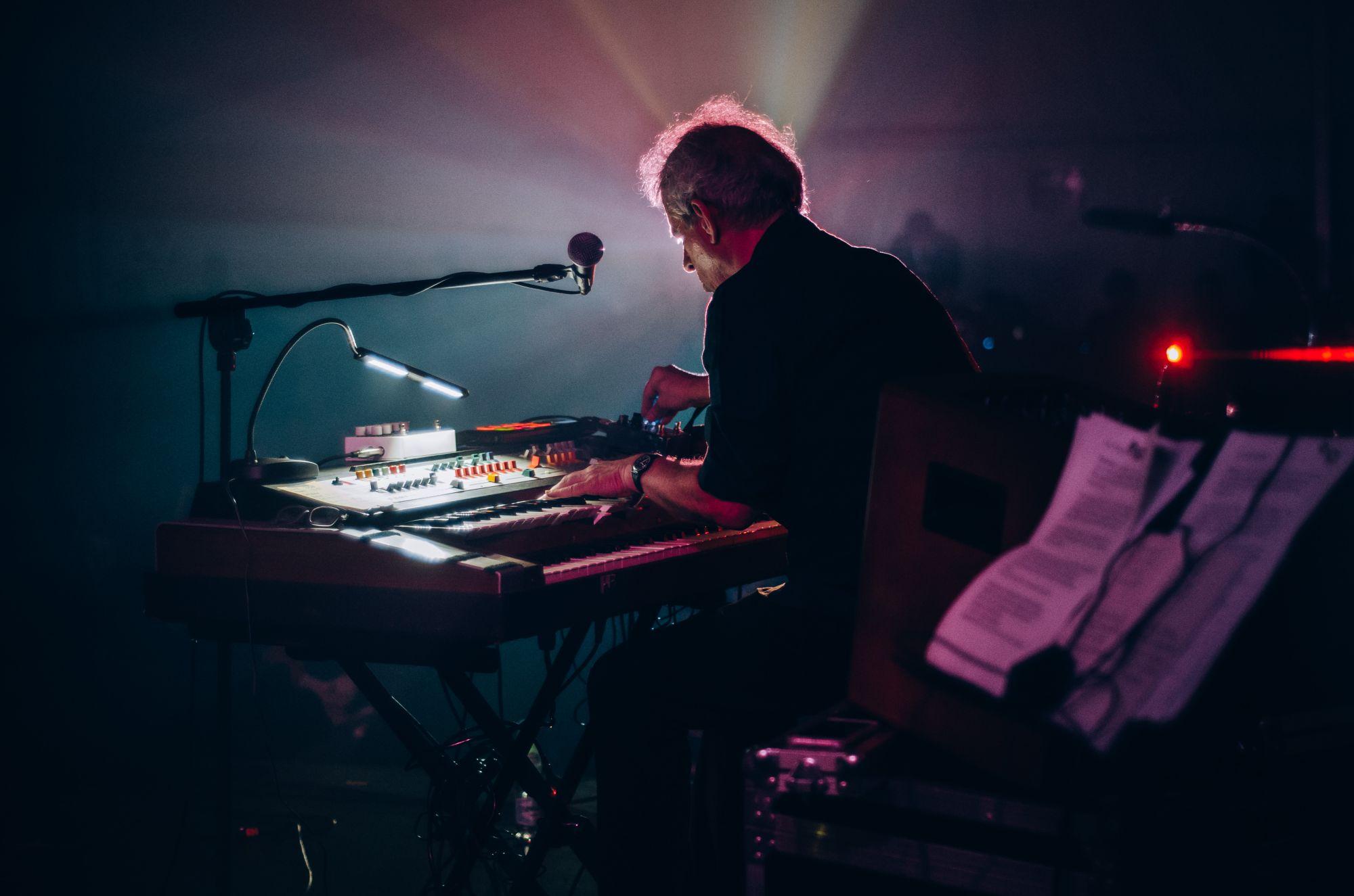 [Zdjęcie z koncertu. Skupiony mężczyzna gra na keyboardzie. Widok z boku. Niesamowite, klimatyczne oświetlenie sceny.]