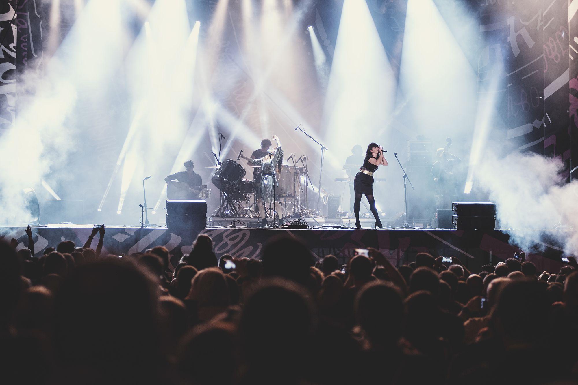 [Wokalista z zaangażowaniem śpiewa na scenie. Za nią w mgle widoczne sylwetki gitarzysty, perkusisty oraz innych członków zespołu. Przed sceną zebrana publiczność.]
