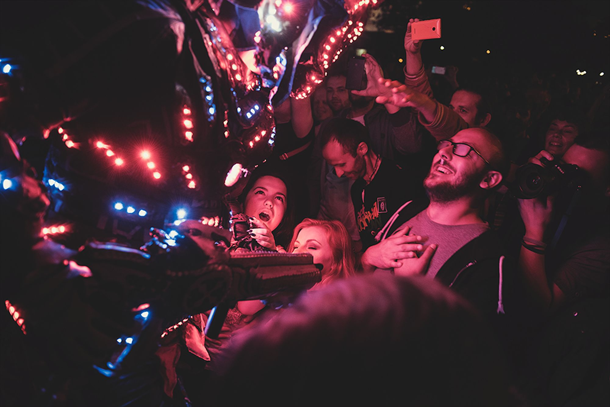 [Koncert Juno Reactor & Mutant Theatre. Na zdjęciu członek zespołu ubrany w kostium z wbudowanymi czerwono-niebieskimi światełkami łapie kontakt z rozentuzjazmowaną publicznością. Widok z boku. Światełka tworzą niepowtarzalny klimat.]