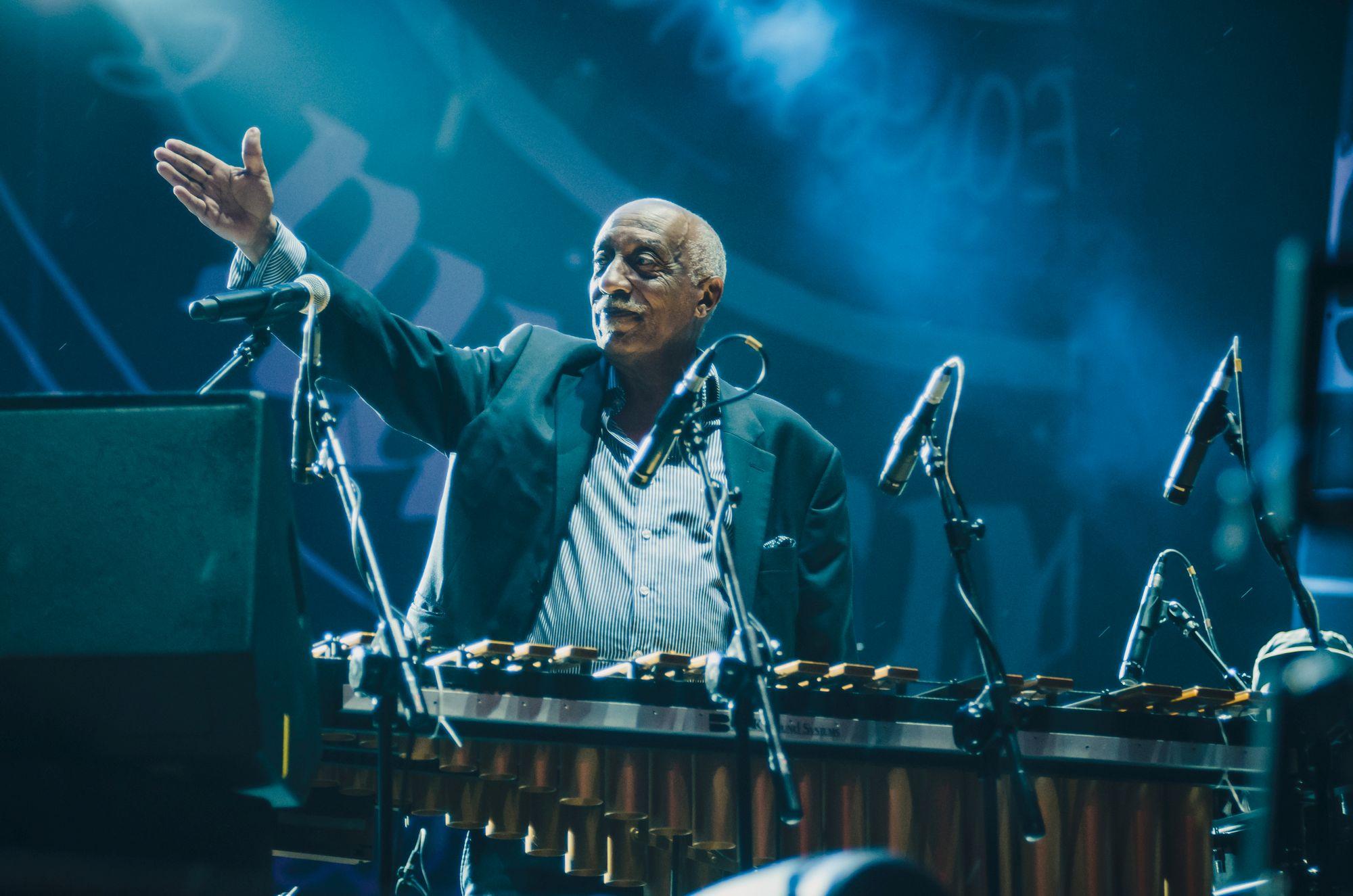 [Na zdjęciu Mulatu Astatke stoi przy klawiszach. Z uznaniem patrzy na kogoś i wskazuje tę osobę uniesioną prawą ręką. Oświetlenie sceny niebieskie.]