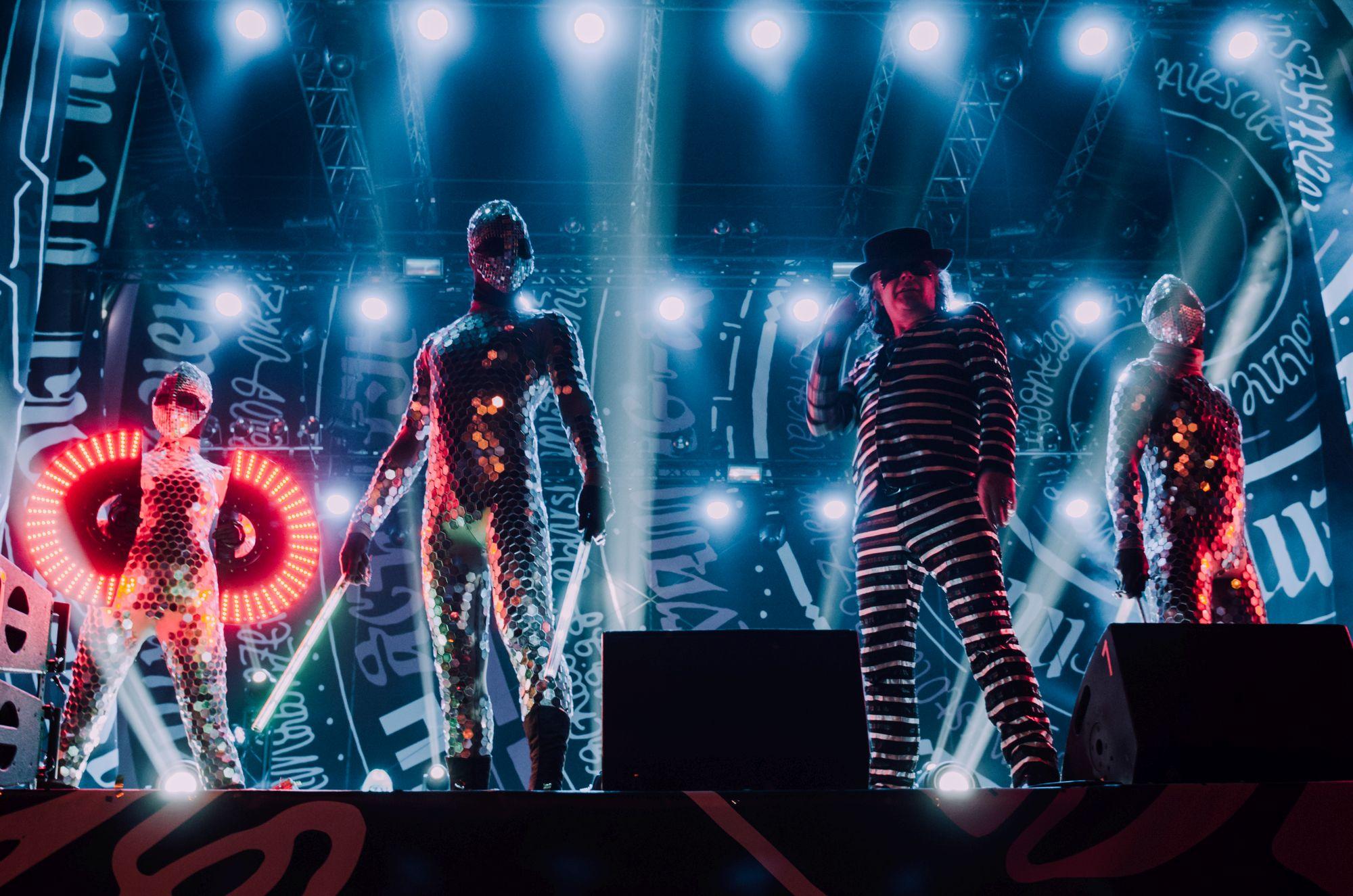 [Fotografia z koncertu Juno Reactor & Mutant Theatre. Czterech członków zespołu na scenie. Trzech z nich ubrani są w niesamowite stroje i maski złożone z cekinów i światełek. Jeden z nich ma kostium z materiału w paski oraz kapelusz na głowie. W tle niebieskie oświetlenie.]