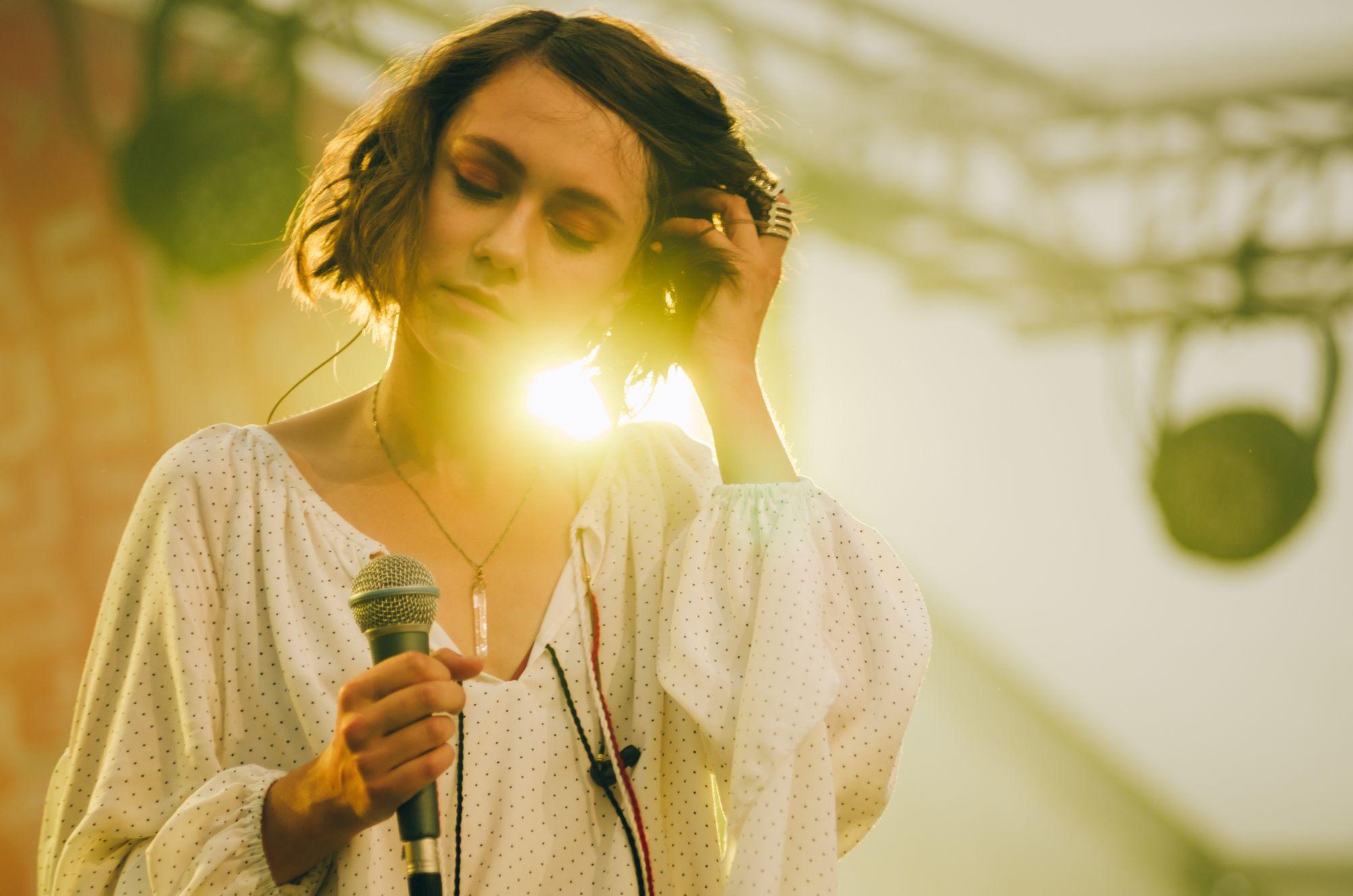 [Koncert Grisly Faye. Zbliżenie na wokalistkę Margarytę Kulichovą. Kobieta ma sentymentalnie przymknięte oczy. W jednej ręce trzyma mikrofon, drugą poprawia włosy. Zza jej ramienia przebija ciepłe żółte światło. Wyczuwa się wyjątkową, magiczną atmosferę.]